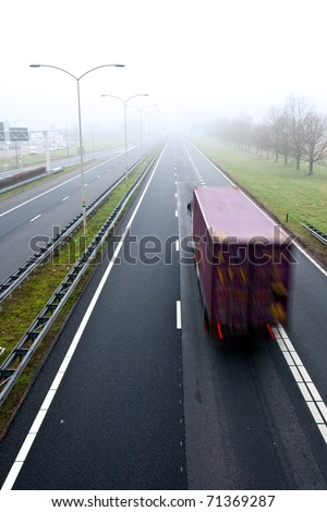 Truck on a highway in misty weather - stock photo