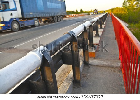 truck on cross-sea red metal bridge against on blue sunset sky background Mountain Highway With Oncoming Trucks In A Wooded Area - stock photo