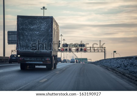 Truck on dirty winter ring road in the evening. - stock photo