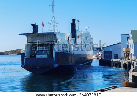Truck on the ferry departs from the pier of Norwegian island - stock photo