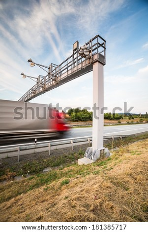 truck passing through a toll gate on a highway (motion blurred image; color toned image) - stock photo