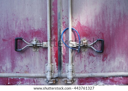 Truck's back old red door with blue lock - stock photo