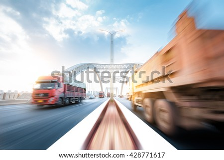 truck speeding through a bridge at sunset, motion blur. - stock photo