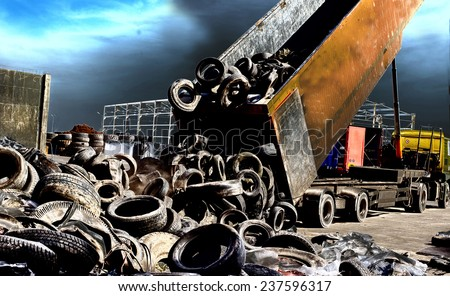 Truck tipping old used tires for recycling - stock photo