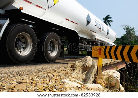 Truck transporting crude oil passes over a bridge in Belize. - stock photo