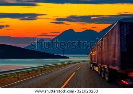 Truck traveling on the road at sunset. - stock photo