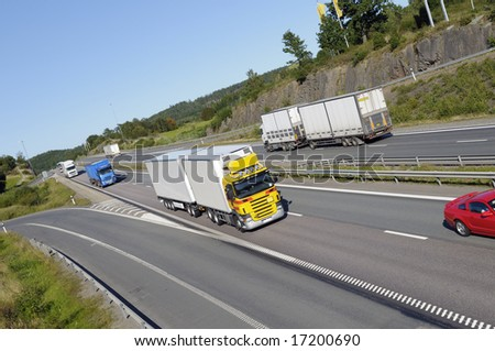trucks and cars on busy highway, tilted perspective and elevated view, all trademarks removed. - stock photo