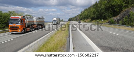 trucks and trafic on a busy highway, head on shot on trucks, panoramic view - stock photo