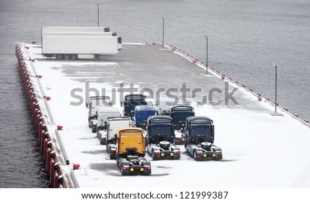 Trucks and trailers waits on snowbound pier in port - stock photo