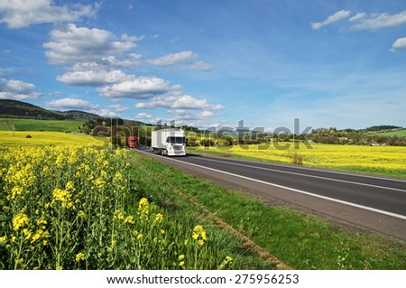 Trucks driving along the asphalt road between rapeseed fields. Wooded mountains in the background. Blue sky with white clouds. - stock photo