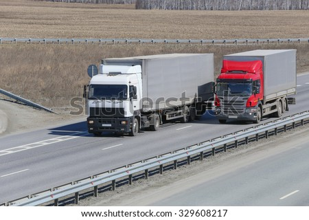 trucks transporting freight on the country highway - stock photo