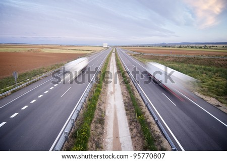 trucks traveling along a straight highway - stock photo