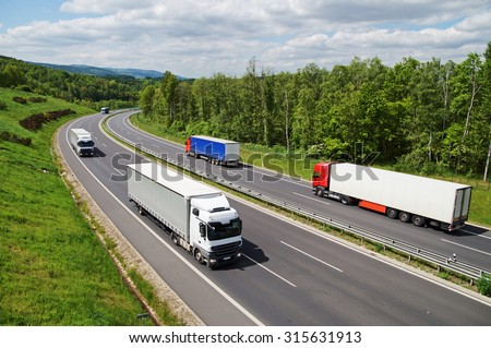 Trucks traveling on an asphalt highway between forests. Wooded mountains in the background. View from above. Sunny summer day. - stock photo