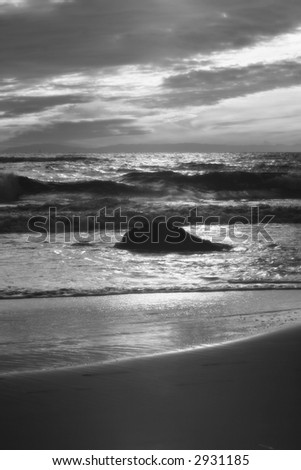 True infrared landscape of a beach with a boulder in the water - stock photo