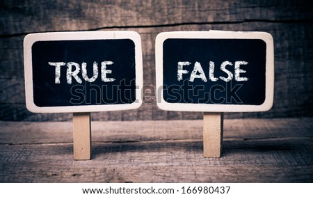 True or False. Small Blackboards with the text - True or False, on wood background  - stock photo