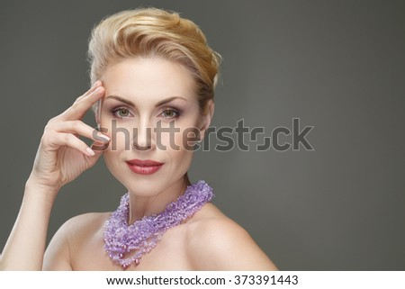 True queen. Horizontal closeup of a beautiful mature woman wearing necklace posing in studio - stock photo