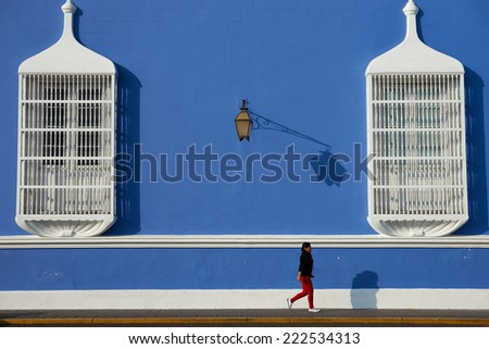 TRUJILLO, PERU - SEPTEMBER 1, 2014: Woman walking past a bright blue and white Spanish colonial style building in the Plaza de Armas of Trujillo in northern Peru. - stock photo