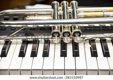 Trumpet on keyboard background - stock photo