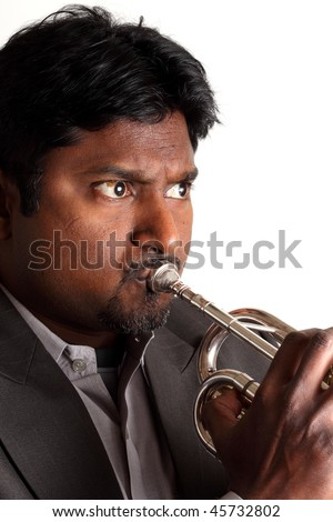 Trumpet player from India with dark skin black hair beard and mustache playing a silver trumpet and wearing a jacket and shirt before a white background - stock photo