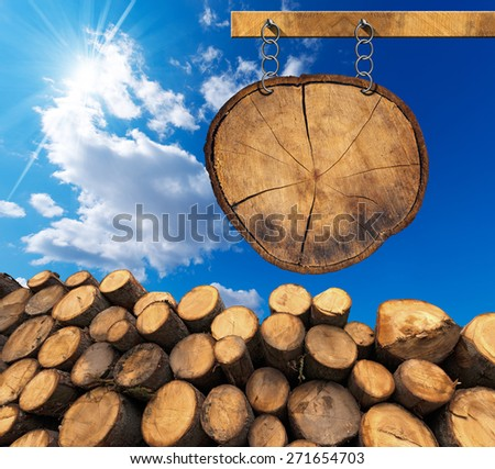 Trunks of trees cut and stacked and empty wooden sign, a section of tree trunk, hanging with metal chain on a wooden pole on blue sky with clouds and sun rays - stock photo
