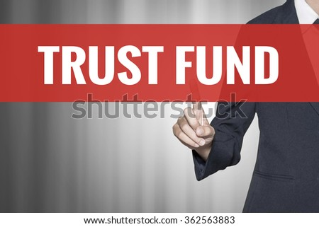 Trust Fund word on virtual screen push by business woman red tab - stock photo