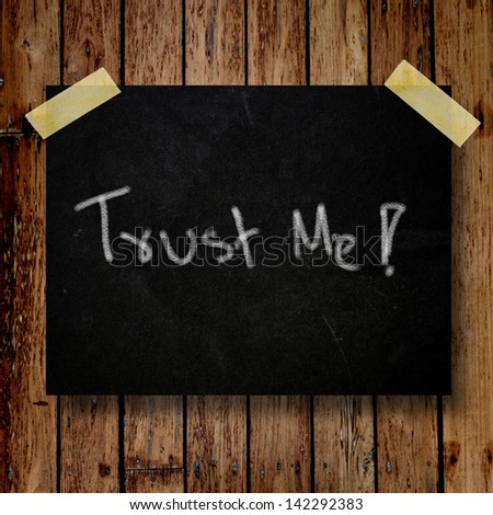 Trust me on message note with wooden background - stock photo