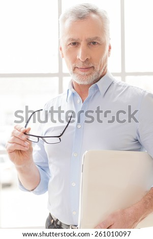Trust to professionals. Confident grey hair senior man in shirt holding laptop and looking at camera while standing in front of the window - stock photo
