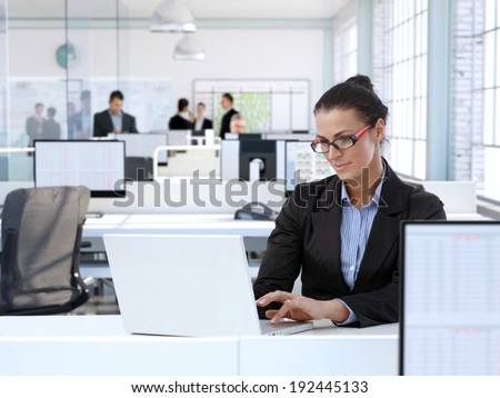 Trustworthy businesswoman working at office desk, using laptop computer. - stock photo