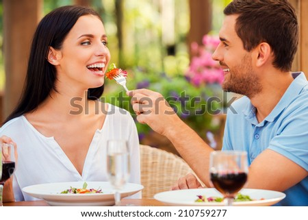 Try my meal! Handsome young man feeding his girlfriend with salad and smiling while both relaxing in outdoors restaurant  - stock photo