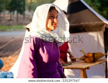 TSIPORI, ISRAEL - JULY 7, 2014: Young woman in lilac medieval dress at sunset during reenactment of Battle of Hattin - last battle of Crusaders' Kingdom of Jerusalem marking its fall in 1187. - stock photo