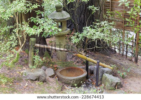Tsukubai Water Fountain with Stone Basin and Bamboo Spigot and Stone Lantern at Portland Japanese Garden - stock photo