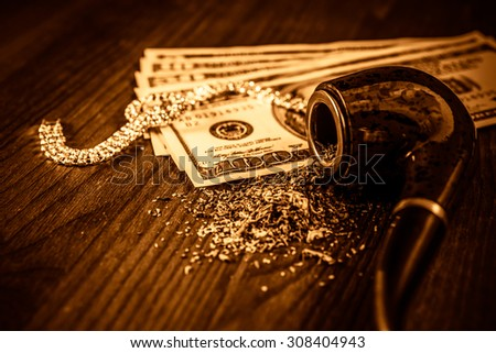 Tube for smoking tobacco and money with jewellery on a wooden table. Focus on the tube, image vignetting and yellow-orange toning - stock photo