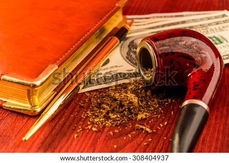 Tube for smoking tobacco and money with leather diary and golden pen on a wooden table. Close up view, focus on the tube - stock photo