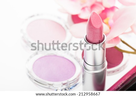 Tube of pretty pink lipstick with matching eye shadow and blusher in a beauty background with focus to the lipstick - stock photo
