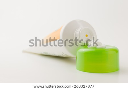 tube with a small amount of the squeezed out white cream - stock photo