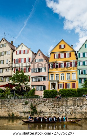 TUBINGEN, GERMANY - MAY 17,2015: A traditional punt is passing the beautiful waterfront of Tubingen (Tuebingen) in the south of Germany. The traditional Stocherkahn (punt) is a typical sight of this - stock photo