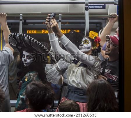 TUCSON, AZ/USA - NOVEMBER 09: Unidentified woman takes a selfie on the Tucson Trolley the All Souls Procession on November 09, 2014 in Tucson, AZ, USA. - stock photo