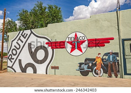 TUCUMCARI, NEW MEXICO - AUGUST 25, 2013: Photo of a mural showing an old Chrysler, the Texaco logo, a Route 66 sign, a woman, and a cowboy on the side of a building - stock photo