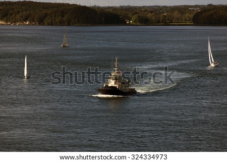 Tug and sailboats in the sun on Little Belt in Denmark - stock photo