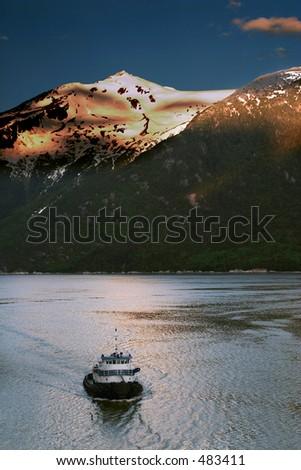 Tug boat coming into Skagway harbor, Alaska, at sunrise. - stock photo