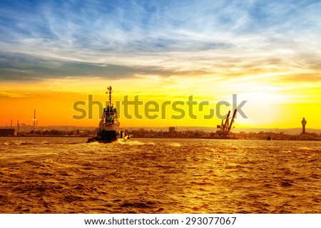 Tug boat returning from the sea to the pier. - stock photo
