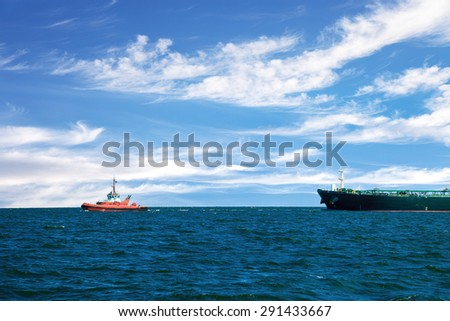 Tug boat towing a tanker ship at sea. - stock photo