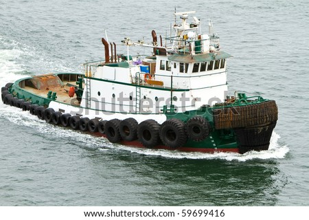 Tug boat traveling through the water - stock photo