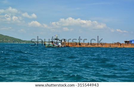 Tug boats towing barges carrying goods from the ocean. - stock photo