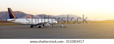 TUG Pushback tractor with Aircraft on the runway in airport. - stock photo