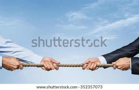 Tug war, two businessman pulling a rope in opposite directions over sky background with copy space - stock photo