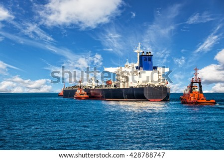 Tugboat towing a tanker ship at sea. - stock photo