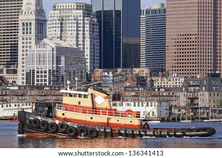 Tugboat with skyscrapers in the background in Boston harbor, MA - stock photo