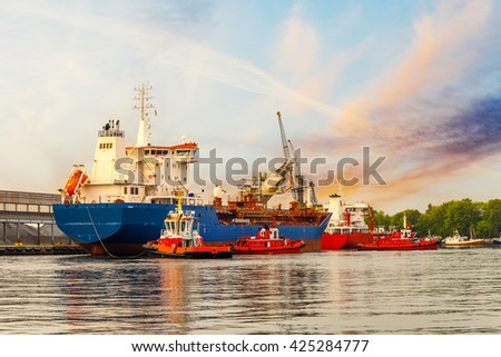 Tugboats maneuver a cargo ship in port of Gdansk, Poland. - stock photo