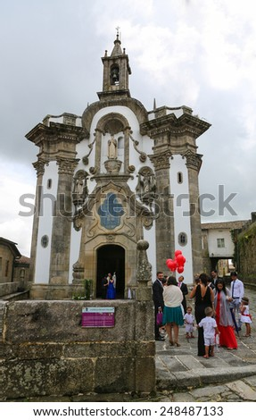 TUI, SPAIN - AUGUST 2, 2014: Guests at a Wedding Ceremony waiting outside the Chapel of San Telmo, in Portuguese baroque style, in Tui, Galicia, Spain. - stock photo
